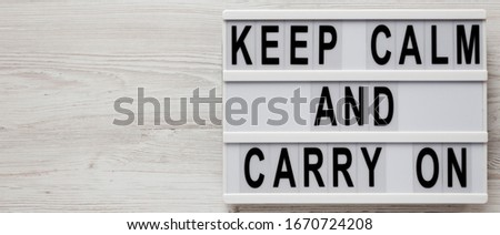 'Keep calm and carry on' words on a modern board on a white wooden background, top view. Overhead, from above, flat lay. Copy space.