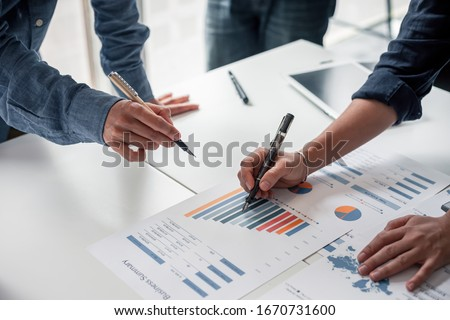 Group of business people meeting together Pointing to the graph assess business profits. Royalty-Free Stock Photo #1670731600
