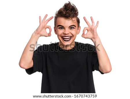Teen boy with spooking make-up making Ok gesture, isolated on white background. Caucasian young teenager in style of punk goth dressed in black smiling and giving OK sign. Happy child showing okay.