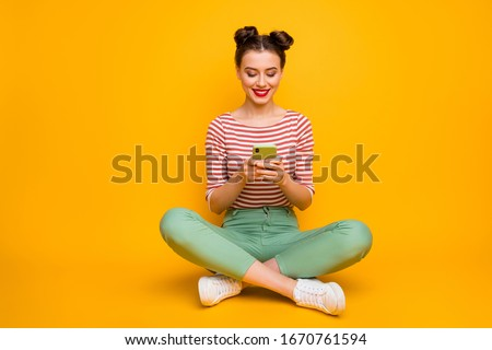 Full length photo of pretty attractive lady sit floor legs crossed hold telephone typing new post blog text wear striped red white shirt green pants shoes isolated yellow color background #1670761594