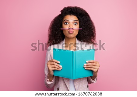 Photo of funny foolish dark skin student lady hold journal book not reading playing pen make fake mustache wear checkered blazer isolated pastel pink color background Royalty-Free Stock Photo #1670762038