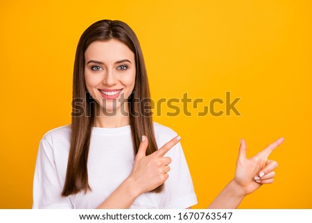Photo of pretty nice business lady directing index fingers side empty space cool amazing offer wear casual white t-shirt isolated vivid yellow color background #1670763547