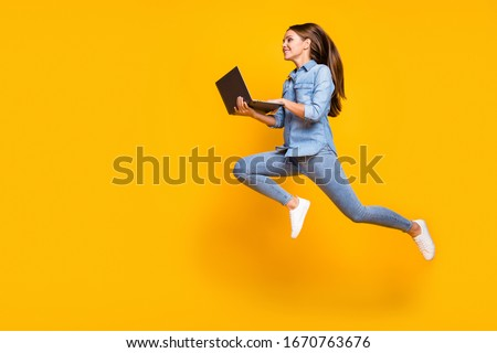Full body profile photo of pretty business lady jump high holding notebook hands hurry work browsing laptop wear casual denim outfit white sneakers isolated yellow color background #1670763676