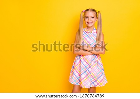 Photo of pretty funny little lady arms folded good mood toothy smiling pretty long tails hairdo enjoy weekend wear checkered plaid summer dress isolated yellow vivid color background #1670764789
