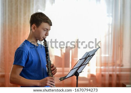 The guy plays the clarinet, looks at the music and plays music in a music school. Royalty-Free Stock Photo #1670794273