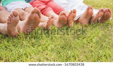 Happy family sitting on grass doing picnic in nature park outdoor - Father, mother, son and daughter having fun together - Travel, parenthood, summer and love concept - Focus on center children feet