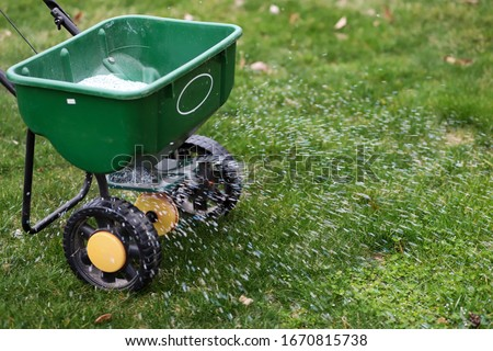 A  seed  and  fertilizer spreader out on a lawn  #1670815738