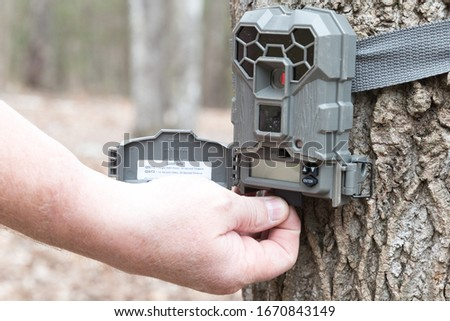 A man taking the SD card out of a motion activated trail camera to check the photos for wild game. Trail cameras are often used by hunters and wildlife enthusiasts to survey the animals in the area.