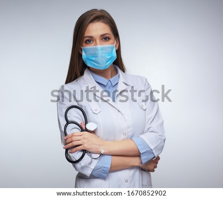 Confident woman doctor wearing medical mask standing with crossed arms. isolated female portrait. #1670852902