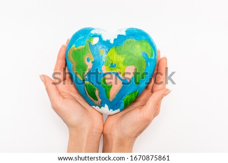 Cropped view of globe in female hands on white background, earth day concept #1670875861
