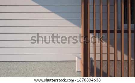 Sunlight and shadow on surface of  wooden trellis in front of white artificial wood and gray Sheetrock wall with part of glass window frame, cheap house materials prices in home architecture concept