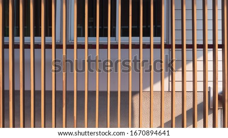 Sunlight on surface of wooden lath in vertical pattern in front of glass windows with white artificial wood and gray sheetrock background, cheap house materials prices in home architecture concept