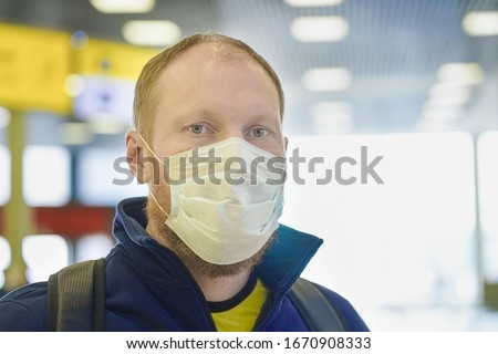 Moscow/Russia - March 2020: European redbeard man in  blue jacket, protective disposable medical mask in airport. Afraid of dangerous N-CoV 2019 influenza coronavirus mutated and spreading in China.  #1670908333