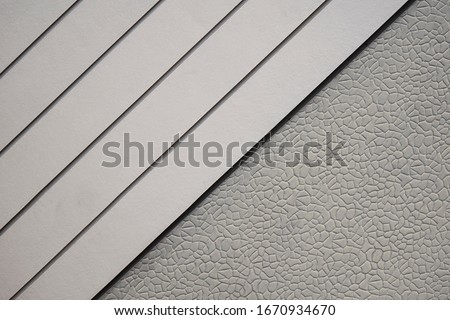 Diagonal view of white artificial wood with stone pattern of gray Sheetrock for wall design background, cheap house materials prices in home architecture concept