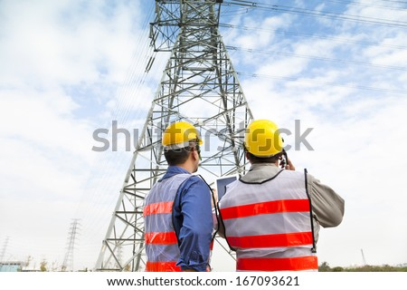 two workers wearing protective helmet works at electrical power station #167093621