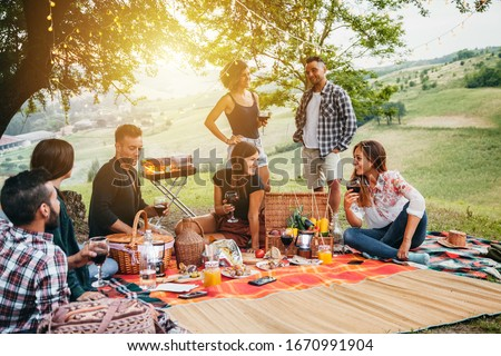 Picnic in the countryside. Group of young friends, at sunset on spring day are sitting on the ground in a park near trees. They drinking red wine and eating grilled meat with barbecue #1670991904