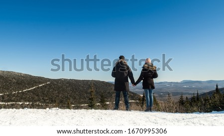 Back view of a couple holding hands in front of a landscape at the Mont Mégantic national park, in winter, Quebec, Canada #1670995306