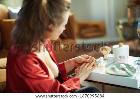 Over shoulder shot of middle age woman in black body lingerie and red bathrobe checking nails near table with toiletries in the modern living room in sunny day. #1670995684