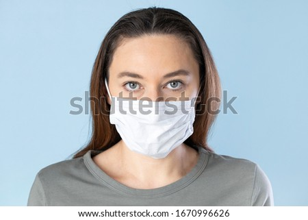 Young woman wearing medical face mask on blue background. Novel Chinese Coronavirus self-protection concept #1670996626
