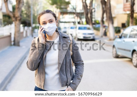 Young woman with face mask on the street. Novel Chinese Coronavirus self-protection concept #1670996629