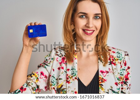 Redhead caucasian business woman holding credit card over isolated background with a happy face standing and smiling with a confident smile showing teeth