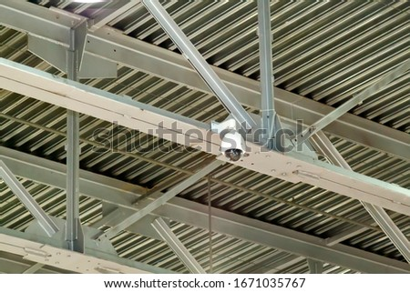 close-up view of a surveillance video camera attached to the joints of metal beams. strong iron construction made of channels that holds the roof #1671035767