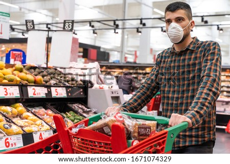 Coronavirus. Food running running out of due to Coronavirus. Empty shelves in the supermarket. Buying panic. Man wearing face mask shopping in supermarket. Protection and prevent measures.  #1671074329