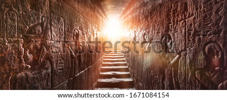 Egypt Edfu temple, Aswan. Passage flanked by two glowing walls full of Egyptian hieroglyphs, illuminated by a warm orange backlight from a door Royalty-Free Stock Photo #1671084154