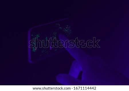 Black UV light exposing germs and bacteria on hand touching lighting switch - Ultraviolet blacklight shows hidden harmful infectious disease - Corona virus, hygiene, sickness and covid-19 concept #1671114442