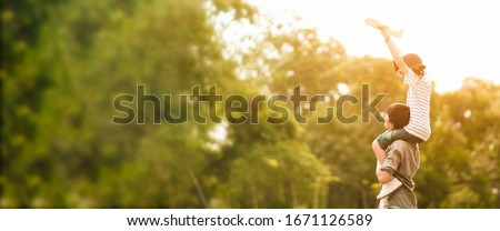 Wide screen of Asian father put his son on his shoulder to play paper plane, spending time together at park in autumn afternoon sunlight, the concept father's day, daddy hero, Family background. Royalty-Free Stock Photo #1671126589