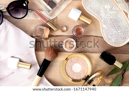 Natural vegan make up flat lay on wooden background - eye shadows, brushes, lipstick, blouse, sun glassses. Royalty-Free Stock Photo #1671147940