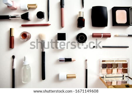 Make up flat lay knolling - cosmetics arrangement on white background. Black, white and pink make up accessories.  #1671149608