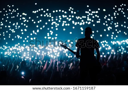 Bass guitarist plays to the crowd of big stadium with flashing lights of their cellphones switched on during the ballad song