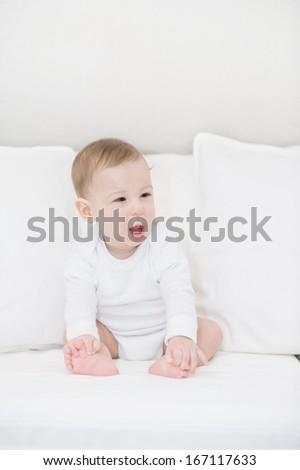 Portrait of crying baby boy on white pillows #167117633