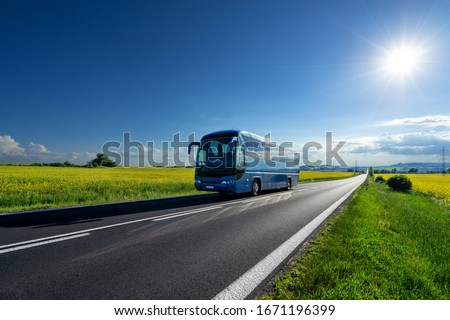Blue bus driving on the asphalt road between the yellow flowering rapeseed fields under radiant sun in the rural landscape #1671196399