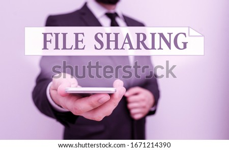 Text sign showing File Sharing. Conceptual photo transmit files from one computer to another over a network Male human wear formal work suit hold smart hi tech smartphone use one hand. #1671214390