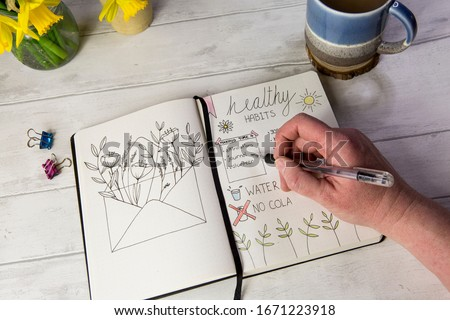 Bullet journal open on self care healthy habits layout pages with hand holding pen. Over shoulder view, fresh white table background, flowers, positive mental health message. Royalty-Free Stock Photo #1671223918