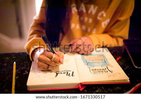 Closeup of young teen girl writing in bullet journal on mood tracker page Royalty-Free Stock Photo #1671330517