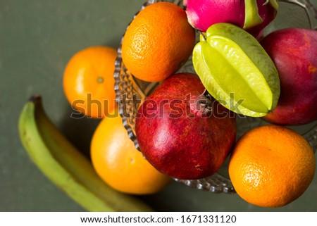 A lot of tropical fruits in a glass vase. Exotic fruits: averrhoa carambola, Pitahaya, Mango, Plantain, tangerines, pomegranate fruit. A lot of tropical fruits in a glass vase. Exotic fruits: averrhoa #1671331120