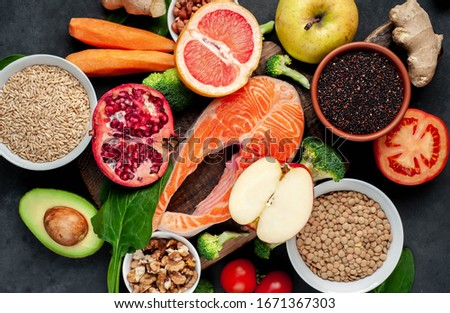 Selection of healthy food:  salmon, fruits, seeds, cereals, superfoods, vegetables, leafy vegetables on a stone background. Healthy food for people. #1671367303