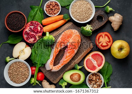 Selection of healthy food: salmon, fruits, seeds, cereals, superfoods, vegetables, leafy vegetables on a stone background. Healthy food for people. #1671367312
