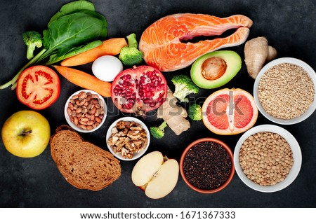 Selection of healthy food: salmon, fruits, seeds, cereals, superfoods, vegetables, leafy vegetables on a stone background. Healthy food for people. #1671367333
