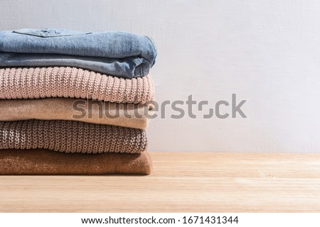 Stack folded colorful sweater with blue jeans clothing on wooden background     #1671431344