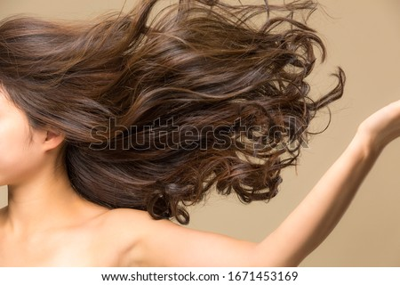 Lively hair on a beige background. Royalty-Free Stock Photo #1671453169