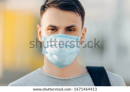 A young man in the background of an open- air building wearing a medical face mask that protects against the spread of coronavirus disease. Close- up of a man with a surgical mask on his face #1671464413