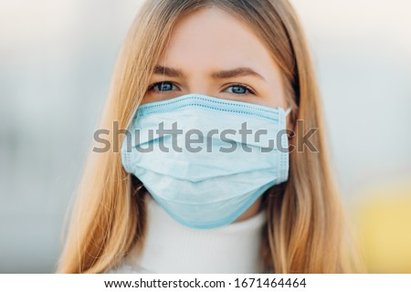 A young girl in the background of a building wears a face mask that protects against the spread of coronavirus disease. Close- up of a young woman with a surgical mask on her face against SARS-cov-2. #1671464464
