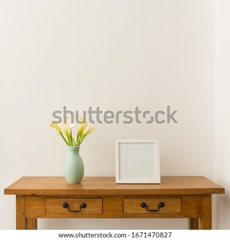White calla lilies in teal vase with blank square picture frame on oak side table against white wall