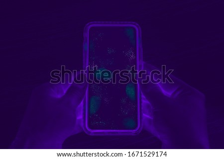 Hands holding cell phone with dirty contaminated touch screen - UV Blacklight exposing infectious bacteria and harmful germs on mobile smartphone display -  Disease, corona virus and hygiene concept Royalty-Free Stock Photo #1671529174
