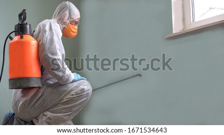 Cleaning and Disinfection at town complex amid the coronavirus epidemic. Professional teams for disinfection efforts. Infection prevention and control of epidemic. Protective suit and mask #1671534643