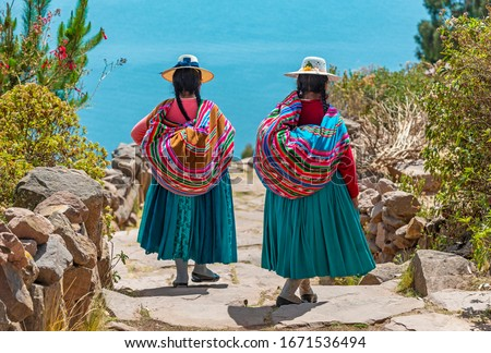 Two indigenous Quechua women in traditional clothes walking down the path to the harbor of Isla Taquile (Taquile Island) with the Titicaca Lake in the background, Peru. #1671536494